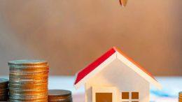 Des pièces de monnaie à coté d'une maison miniature